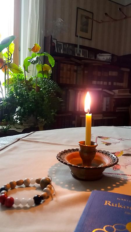 tuohus palamassa. Vieressä rukouskirja ja rukoushelmet.